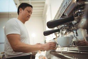 Barista making espresso in coffee shop