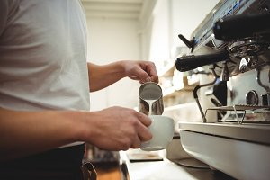 Male barista pouring milk into coffee cup at cafe