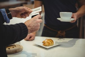 Customer making payment with smartphone in coffee shop