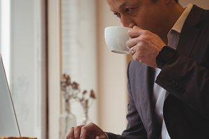 Businessman drinking coffee while using laptop