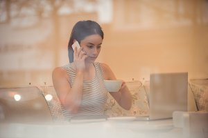 Businesswoman talking on phone while having coffee