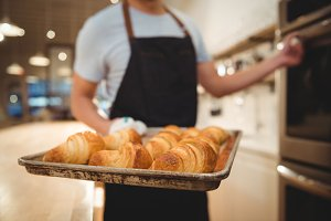 Barista holding tray of freshly baked croissants