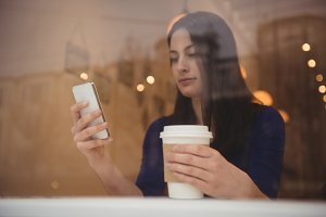Woman holding disposable coffee cup while using phone