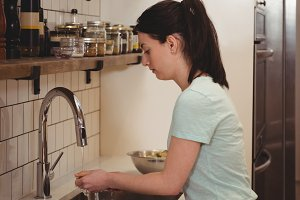 Female chef washing carrot under the tap in professional kitche