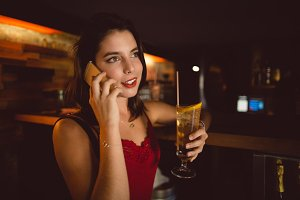 Beautiful woman talking on mobile phone while having cocktail at counter