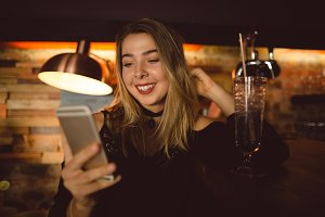 Beautiful woman using mobile phone while having cocktail at counter