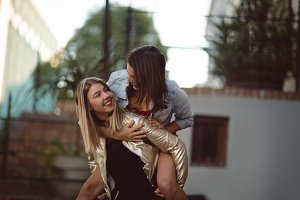 Woman giving piggy back to her friend