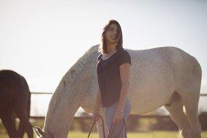 Beautiful woman holding horse rein in farmland
