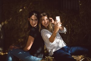 Friends taking selfie on mobile phone in stable