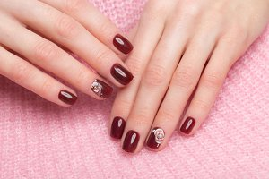 Shot beautiful manicure with flowers on female fingers. Nails design. Close-up