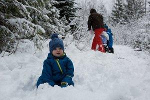 Portrait of cute boy sitting on snow