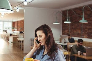 Female executive talking on mobile phone while having coffee at desk