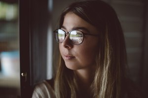 Close-up of beautiful woman looking through window