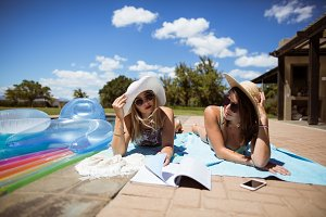 Beautiful women reading book while sunbathing