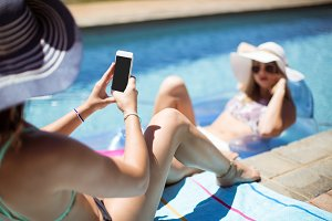 Woman clicking picture on her friend in swimming pool