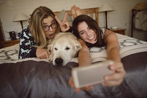 Happy friends with dog taking selfie on mobile phone
