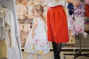 Shopping for kids. Little girl admires herself in front of the mirror