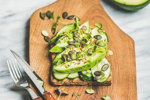 Healthy green veggie breakfast concept with sandwich on wooden board