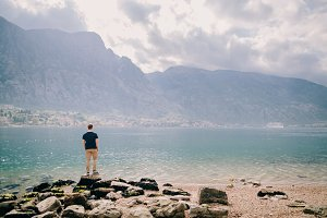 man travel rocky beach and mountains