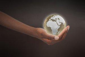 Feminine hand holding a planet globe