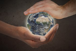 Two hands protecting a glowing planet globe