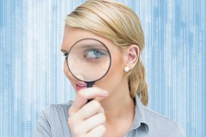 Blonde woman looking through magnifying glass