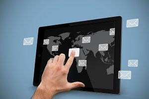 Hand selecting email symbol on tablet pc with world map background
