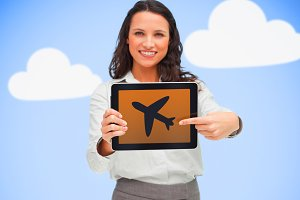 Woman standing holding a tablet pc showing on a plane symbol on blue cloud background