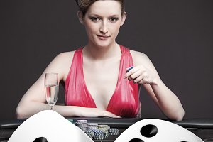 Woman playing roulette with champagne in casino