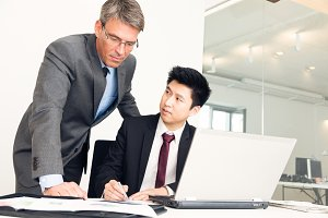 Manager And Employee Looking At Documents
