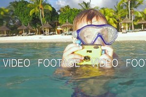 Child bathing in ocean and taking photos with waterproof camera