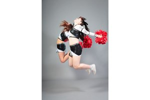 Two Cheerleaders Jumping