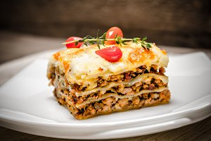 Portion of lasagna on the wooden tab