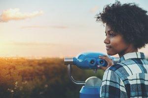 Black girl with binocular in park