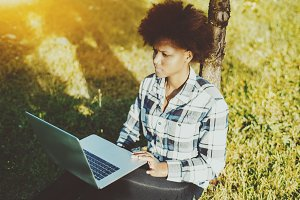 Girl sitting on grass with laptop