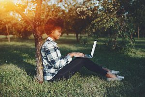 Afro girl in park with laptop