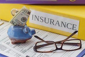 Clean insurance form, folders, pen, piggy bank and glasses