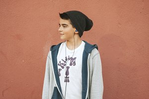 urban boy with headphones on the wall