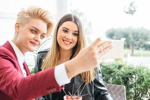 Young girlfriends taking selfie