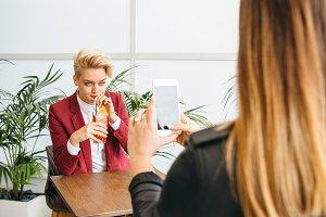 Woman taking photo of girlfriend