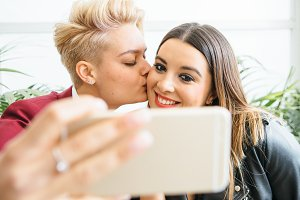 Smiling lesbian couple taking selfie