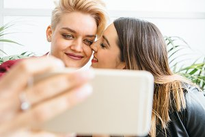 Gentle lesbian couple with smartphone