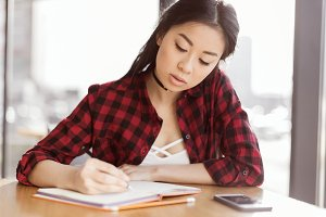 asian student writing in diary