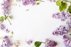Flat lay top view photo of spring composition. Frame made of lilac flowers on white background.