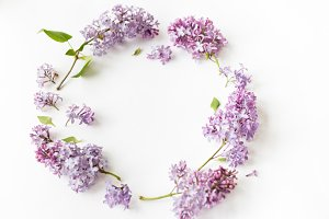 Flat lay top view photo of spring composition. Wreath made of lilac flowers on white background.