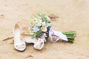 Beautiful boho composition with a bridal bouquet and wedding shoes