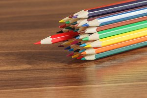 Heap of colored pencils on the wooden background
