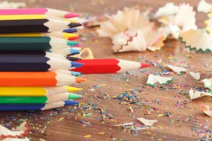 Heap of colored pencils, wooden background
