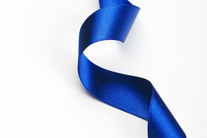 Blue ribbon on white background. Copy space. Vertical shoot.