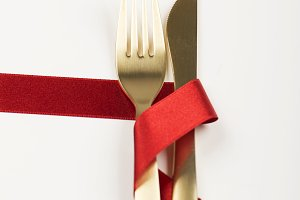 Fork and knife of golden color with a red ribbon on white background. Decor. Vertical shoot.